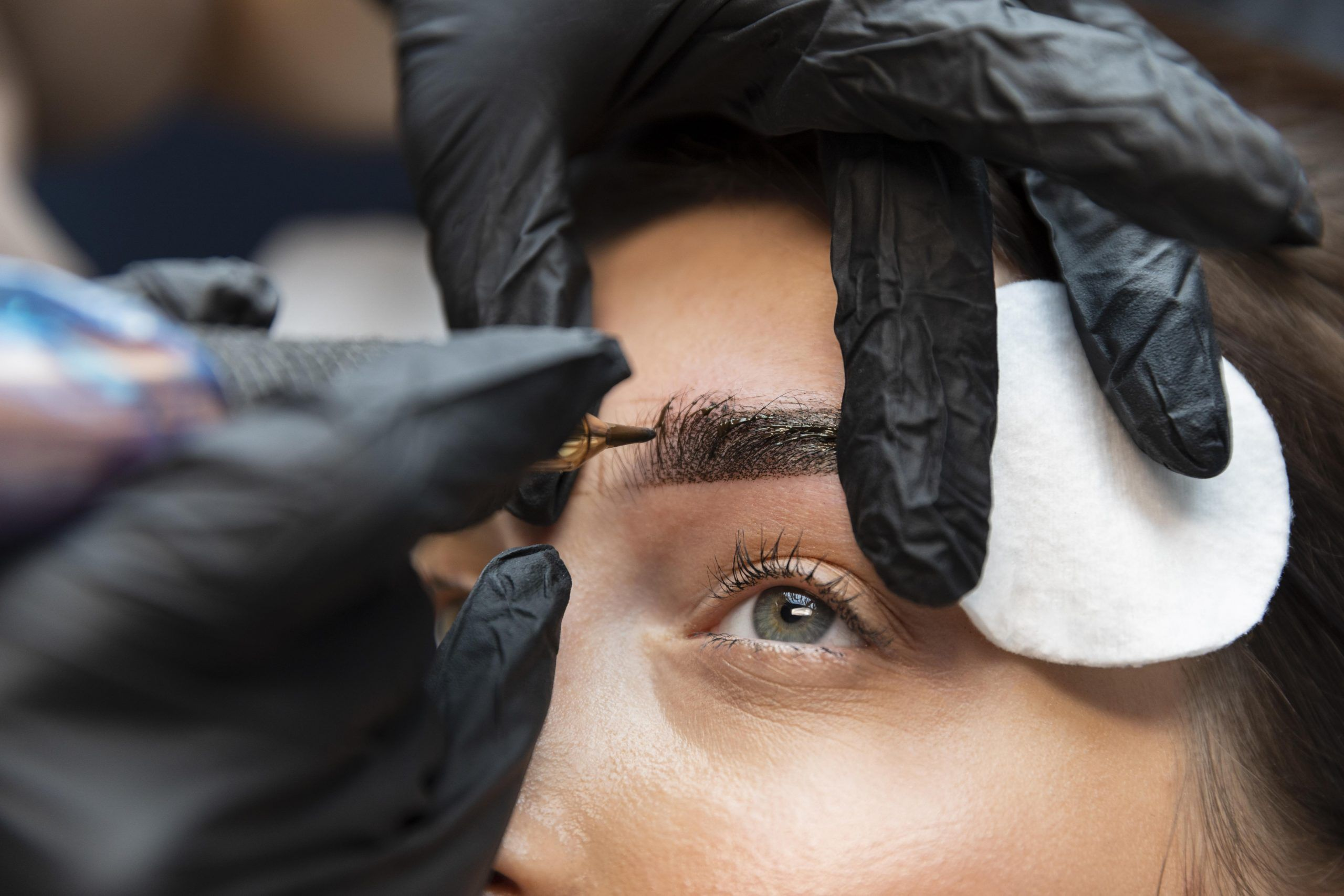 young woman getting beauty treatment for her eyebrows scaled