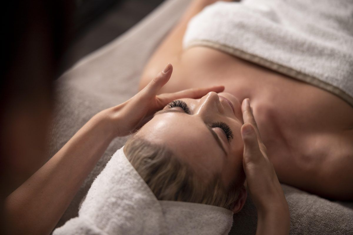 young woman massaging her client s face